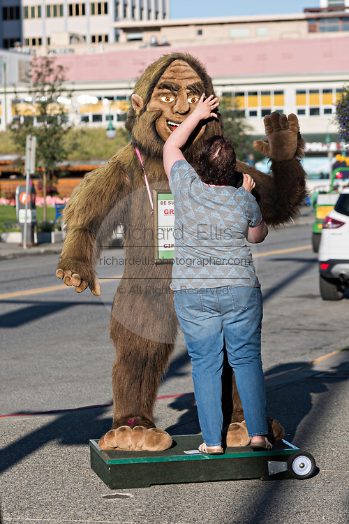 A worker adjusts a giant stuffed Bigfoot or Sasquatch to attract tourists at a shop along 4th Avenue in downtown Anchorage, Alaska.