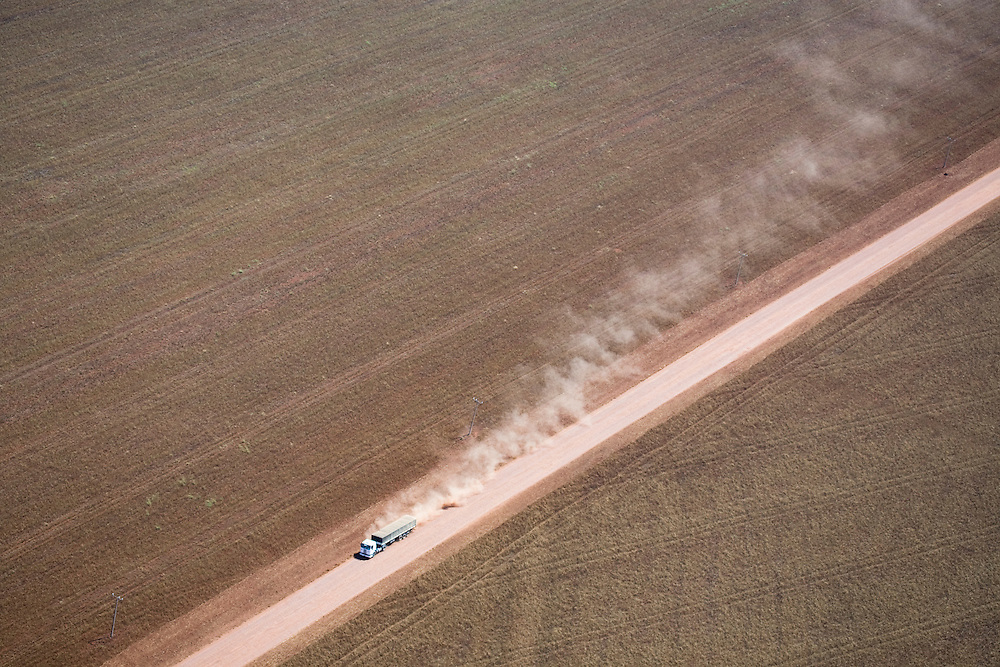 A semi truck leaves a cloud of dust and dirt as it drives throug farmland in the Tangana Da Serra region of Mato Grosso, Brazil, August 9, 2008. Daniel Beltra/Greenpeace