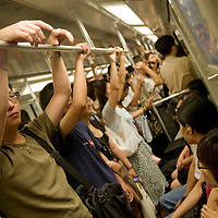 Asia, China, Shanghai, Passengers crowded onto Metro underground subway train near People's Square during morning rush hour.
