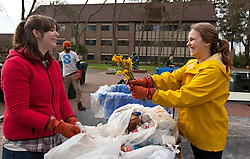 Savannah Phalan '15, right, offers Sarah Wheeler 15, a slightly used bouquet of flowers while working on a table of trash during Garbology on Red Square, where grash from different locations is sorted to determine how much is recycleable or compostable at PLU on Tuesday, March 17, 2015. (Photo: John Froschauer/PLU)