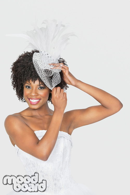 Portrait of beautiful African American bride wearing feather fascinator over gray background
