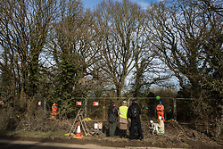Harefield, UK. 7 February, 2020. Activists observe HS2 engineers erecting Heras fencing to surround three environmental activists from Extinction Rebellion who have climbed a veteran oak tree close to the Harvil Road wildlife protection camp in order to try to protect it from felling. HS2 are expected to try to fell large numbers of mature trees in the immediate vicinity over the weekend even though the high-speed rail link is still awaiting Boris Johnson's approval.