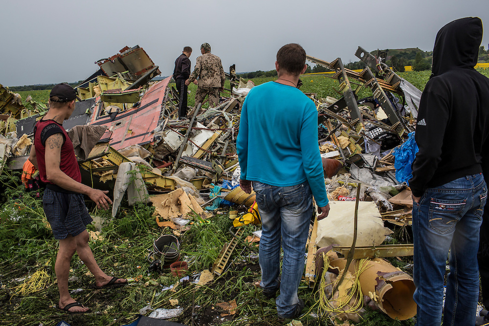 RASSIPNOYE, UKRAINE - JULY 18: Men search the wreckage of a commercial passenger plane which was shot from the sky by a missile the previous day on July 18, 2014 in Rassipnoye, Ukraine. Malaysia Airlines flight MH17 travelling from Amsterdam to Kuala Lumpur has crashed on the Ukraine/Russia border near the town of Shaktersk. The Boeing 777 was carrying 280 passengers and 15 crew members. (Photo by Brendan Hoffman/Getty Images) *** Local Caption ***