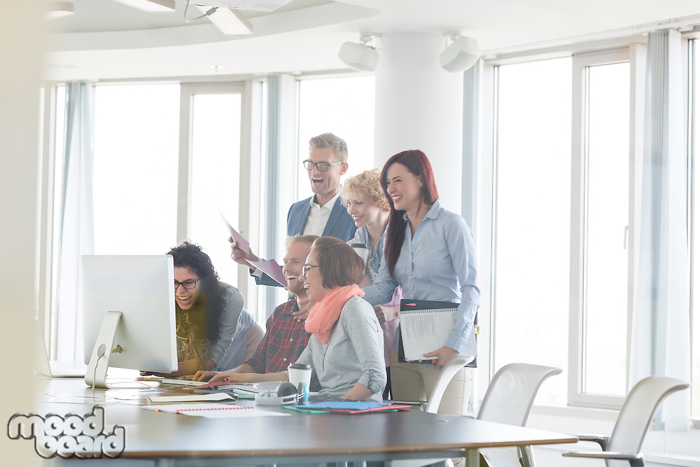 Cheerful businesspeople working together at conference table