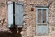 In afternoon heat, baked hard paint textures on village closed wooden shutters and doorway, on 26th May, 2017, in Villerouge-Termenes, Languedoc-Rousillon, south of France