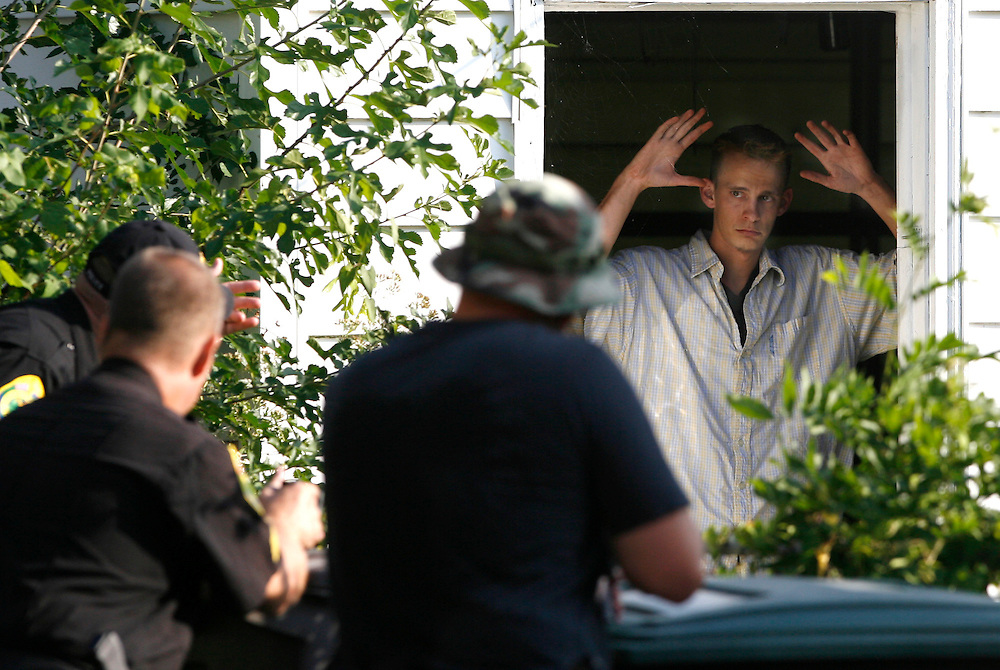 A suspect surrenders to police after he barricaded himself in a shed behind a house on Kilgore Avenue Monday afternoon. The standoff lasted over an hour and ended when officer Amy Kesler talked him out of the building.