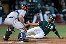 OAKLAND, CA - JULY 19:  Marcus Semien #10 of the Oakland Athletics is tagged out at home plate by Evan Gattis #11 of the Houston Astros during the second inning at the Oakland Coliseum on July 19, 2016 in Oakland, California. (Photo by Jason O. Watson/Getty Images) *** Local Caption *** Marcus Semien; Evan Gattis