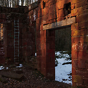"""Rays of light from the setting sun illuminate the ruins of Seneca Stone Cutting Mill.<br /> <br /> Located on the banks of Seneca Creek and the Potomac River, Seneca Quarry provided Washington D.C. with a steady supply of sandstone that was both durable and beautiful for itís unique bright-crimson hue. This """"Seneca redstone"""", finely cut and polished in this mill, is everywhere throughout the District, from the Smithsonian Castle, Cabin John Bridge, Arlington National Cemeteryís boundary wall and Luther Place Church in Thomas Circle to numerous houses throughout Dupont Circle and Adams Morgan. <br /> <br /> Beginning in the 1870ís, The millís fortunes declined through financial mismanagement and flood damages. By the turn of the century the quality of the quarried stone had degraded significantly, and the victorian architecture that relied on material such as seneca redstone fell out of popularity. The Seneca quarry shut down operations for good in 1901, leaving the mill to crumble and decay."""