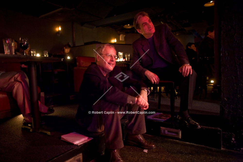 Current US poet laureate Charles Simic, left, and former laureate, Robert Pinsky, right, sit off-stage while listening to jazz between readings of some poetry during a collaboration with jazz musicians at the Jazz Standard in New York, U.S. 1/8/08.