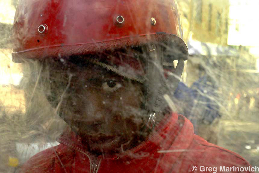 SOUTH AFRICA JOHANNESBURG July 14, 2005. Eighteen year old private security guard Thulani Ncube behind his shield on a 'Red Ants' security detail on Bree Street where several hundred people, including illegal Zimbabwean immigrants, were evicted from an office block being illegally used as apartments in downtown Johannesburg July 14, 2005. Johannesburg municipality uses the Red Ants to privatise the politically unpopular task of evictions of people living in unsuitable buildings and shanty towns. Many of the deserted or derelict downtown office and apartment blocks have been invaded by people desperate for low-priced living space. Greg Marinovich / South Photographs
