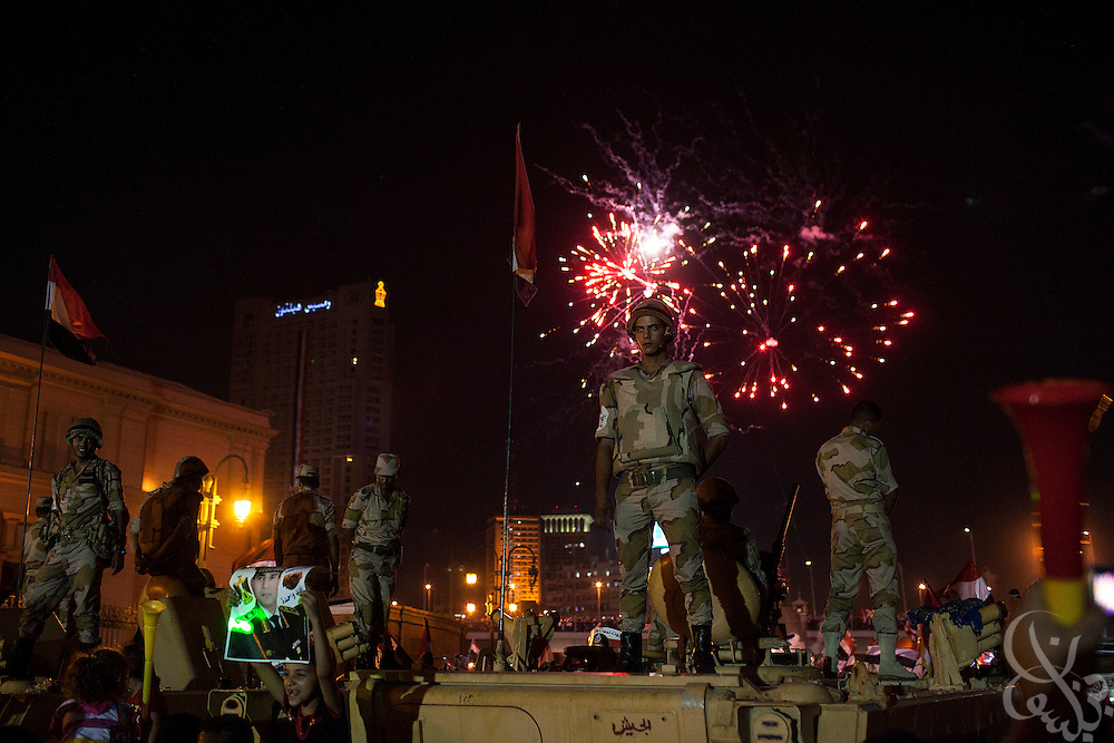 "Fireworks burst in the sky behind as Egyptian soldiers stand atop an APC during mass demonstrations called for by Gen. Abdel Fattah El Sissi, the head of Egypt's military, in the Tahrir Square area of downtown Cairo Egypt on Friday July 26, 2013. EL Sissi had asked Egyptians to take to the streets on Friday to show the world that he had a mandate to deal with ""violence and terrorism"", ahead of what many believe is a planned crackdown on the Muslim Brotherhood political group."
