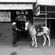 25 Aug 2003, Vancouver, British Columbia, Canada --- A Vancouver police officer and his horse outside of a pub in the Downtown Eastside.  The Downtown Eastside has become a haven for drug addicts and dealers.  Drugs like heroin and crack cocaine are used openly on the street and the neighborhood has the dubious distinction of being the poorest area in Canada.  The area also boasts the first safe injection site for IV drug users in North America.  The Downtown Eastside is reported to have 10,000 drug addicts living in its rooming houses, low rent apartments, and streets.  --- Image © Christopher J. Morris  NO MODEL RELEASE FOR THIS PHOTO