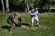 Two men, both Jamaican migrant workers, play cricket near their temporary home. They were enjoying their Sunday afternoon after working in the morning at a large nearby greenhouse.