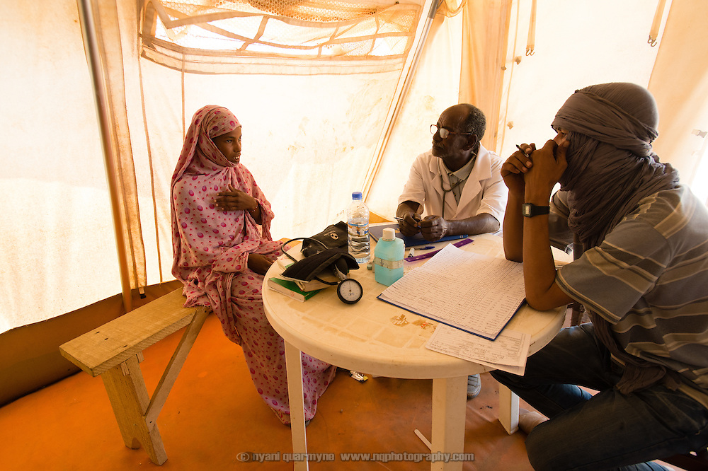Nurse, Hamaty Chenane (centre), and translator, Mohamed Ag Hamata (right), during a consultation with Rahma Walet Abbo (17) at a Médecins Sans Frontières (MSF) health centre at the Mbera camp for Malian refugees in Mauritania on 3 March 2013.