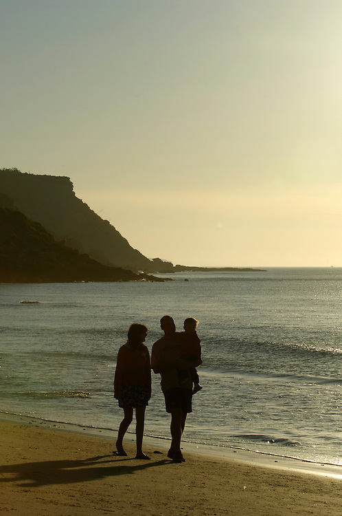 A family on an early morning walk on the beach at Bergau on the Algarve, Portugal.