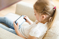 Rear view of girl playing hand-held video game at home