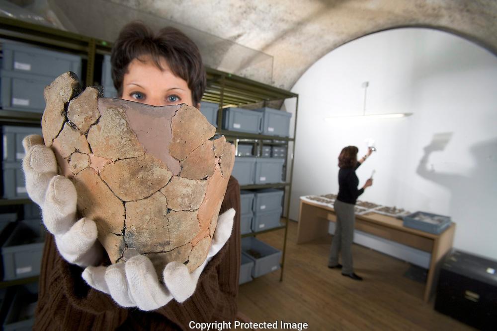 """Sophie Brocard archeoeogue, montre recipient en terre cuite de l'Age du Fer (800-750 av. J.-C.), provenant des fouilles de Varen Sportplatz (Haut-Valais), dans les caves de Musees le mardi 12 septembre 2005 a Sion. A l'occasion des 175 ans de leur creation, les Musees cantonaux du Valais organisent, sous le titre """"Les chambres secretes des Musees"""", differentes manifestations echelonnees sur quatre annees dans le but de mettre a jour les activites souterraines des musees. Le deuxieme volet de la serie, Voyage au coeur des reserves, aura lieu du 12 novembre au 1er decembre 2005 et sera entierement consacre a la conservation et a la restauration des objets confies aux Musees cantonaux. Pour montrer au public le trajet parfois complexe des objets, de leur arrivee au musee jusqu'a leur mise en valeur a l'occasion d'expositions, mais egalement pour lui faire decouvrir la diversite des professionnels engages dans la restauration et la conservation des objets 'dormant' dans les reserves, les Musees cantonaux proposent toute une serie de visites de reserves et d'ateliers de restauration specialises dans differentes techniques. (PHOTO-GENIC.CH/ OLIVIER MAIRE)"""