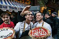 "NAPLES, ITALY - 8 DECEMBER 2017: Gino Sorbillo (39, center), a Master Pizzaiuolo (pizza chef) and owner of Pizzeria Gino Sorbillo,  together with his brother Toto (right) pose for a selfie with a customer, to celebrate the art of Pizzaiuolo added to Unesco's list of Intangible Cultural Heritage of Humanity, here by his pizzeria in Naples, Italy, on December 8th 2017.<br /> <br /> On Thursday December 7th 2017, UNESCO added the art of Neapolitan ""Pizzaiuolo"" to its list of Intangible Cultural Heritage of Humanity.<br /> <br /> The art of the Neapolitan 'Pizzaiuolo' is a culinary practice comprising four different phases relating to the preparation of the dough and its baking in a wood-fired oven, involving a rotatory movement by the baker. The element originates in Naples, the capital of the Campania Region, where about 3,000 Pizzaiuoli now live and perform. Pizzaiuoli are a living link for the communities concerned. There are three primary categories of bearers – the Master Pizzaiuolo, the Pizzaiuolo and the baker – as well as the families in Naples who reproduce the art in their own homes. The element fosters social gatherings and intergenerational exchange, and assumes a character of the spectacular, with the Pizzaiuolo at the centre of their 'bottega' sharing their art.<br /> <br /> In Naples, pizza makers celebrated the victory by giving away free pizzas."