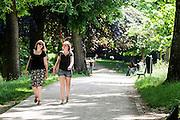In het park Lepelenburg in Utrecht lopen twee meisjes genietend van de zon te praten in zomerse kleding.<br /> <br /> In park Lepelenburg in Utrecht two girls are walking while enjoying the sun.