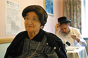 Elderly residents having discussions over lunch in Schonfeld square, an Orthodox Jewish (Kosher) old peoples care home run by Agudas Israel Housing Association, Stamford Hill, London.