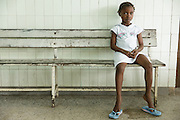 A girl sits on a bench in a waiting room at the Koumassi General Hospital in Abidjan, Cote d'Ivoire on Friday July 19, 2013.