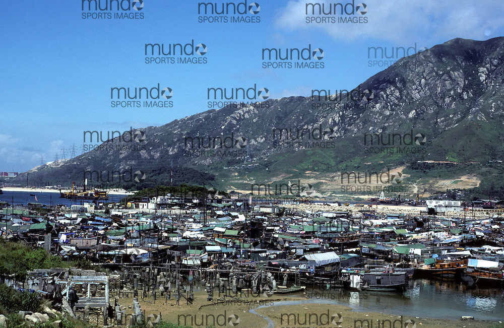 A collection of junks and houses for the poor and informal sector workers near Hong Kong in 1981. The community is located in a part of Hong Kong called the 'New Territories'. Much of the New Territories were, and to a limited extent still are, rural areas. Attempts at modernising the area were not extensive until the late 1970s, in which many new towns were built to accommodate the overspill from the urbanized areas of Kowloon and Hong Kong Island. Despite rapid development of the new towns which has resulted in a population of over 3 million, the Hong Kong Government confines built-up areas to a few areas and reserves large parts of the region as parkland.