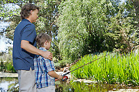 Side view of father and son fishing countryside