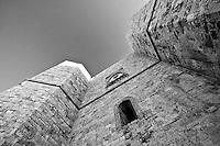 Castel del Monte - Puglia - Esterno. Castel del Monte è un edificio del XIII secolo costruito dall'imperatore Federico II in Puglia, nell'attuale frazione omonima facente parte del vicino comune di Andria. Inserito nel 1996 tra i monumenti patrimonio dell'Unesco, Castel del Monte conserva da secoli il mistero della sua funzione. La forma a pianta ottagonale ha ispirato le più diverse ipotesi sul motivo della sua costruzione: scartata la funzione di torretta di difesa (per la mancanza di strutture militari e delle scale a chiocciola costruite in senso antiorario, a svantaggio dei soldati costretti a impugnare le armi con la mano sinistra), scartata la funzione residenza di caccia a causa della mancanza di stalle, si accredita la funzione di tempio, anche per via dei simboli che caratterizzano l'intera costruzione.
