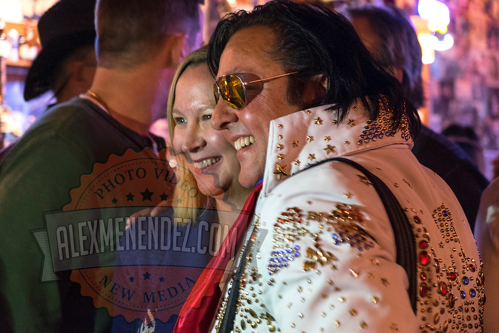 An Elvis impersonator poses with a patron in a bar on Music Row in downtown Nashville, Tennessee on Friday, November 13, 2015. (Alex Menendez via AP)