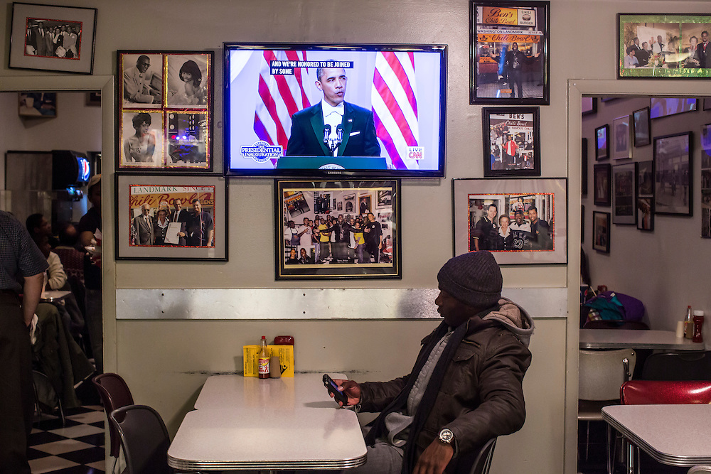 Dewayn Lewis of Washington, DC, checks his phone as President Barack Obama speaks at the Inaugural Ball at Ben's Chili Bowl, a local institution which President Barack Obama has visited, on Monday, January 21, 2013 in Washington, DC.