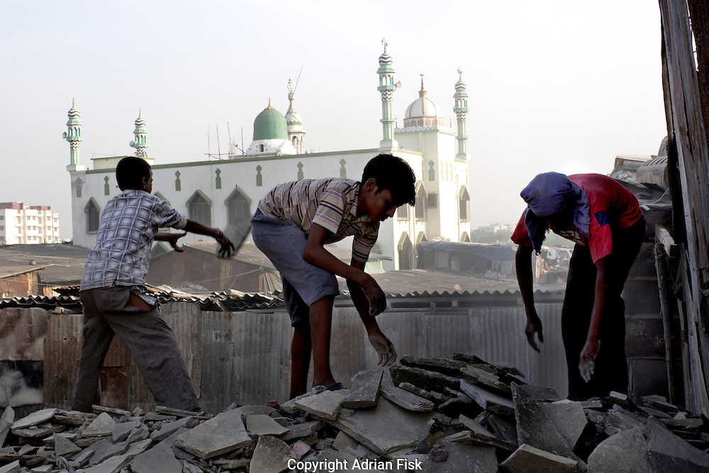 Boys throw old paving slabs down to a machine that grinds the slabs and then uses the powder to make cement on 21st Oct 2006. In the background Dharavis main mosque can be seen.