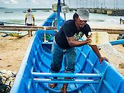 18 JULY 2016 - KUTA, BALI, INDONESIA:  A man gets his small outrigger canoe ready to go out to sea to go fishing at Pasar Ikan pantai Kedonganan, a fishing pier and market in Kuta, Bali.   PHOTO BY JACK KURTZ