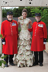 © Licensed to London News Pictures. 21/05/2012. London, England. Model wearing a paper dress with two Chelsea Pensioners. RHS Celsea Flower Show 2012 - Press Day. Photo credit: Bettina Strenske/LNP