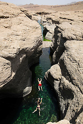 Tourists swimming at Hatta Rock Pools natural fresh water springs in Oman