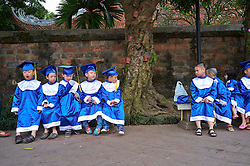 A Kindergarten class dressed in graduation caps and gowns sits on benches during an excursion to the Temple of Literature in Hanoi, Vietnam, Southeast Asia