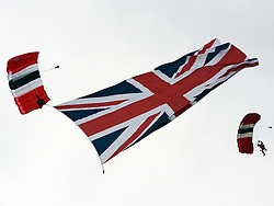 © Licensed to London News Pictures. 02/06/2012. London, UK. A member of The Red Devil parachute display team carries a large Union Flag. HRH Queen Elizabeth at The Investic Derby Festival today 2nd June 2012. The Royal Jubilee celebrations. Great Britain is celebrating the 60th  anniversary of the countries Monarch HRH Queen Elizabeth II accession to the throne this weekend Photo credit : Stephen Simpson/LNP