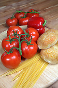 Italian style ingredients including tomatoes, uncooked linguini, onion and garlic with dinner rolls on a wood background - with copy space right