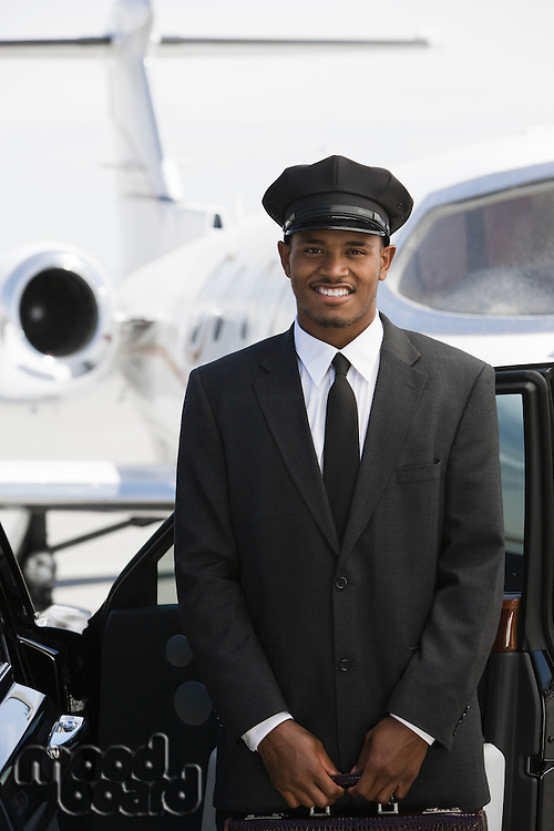 Portrait of mid-adult chauffeur standing in front of limousine and private jet.