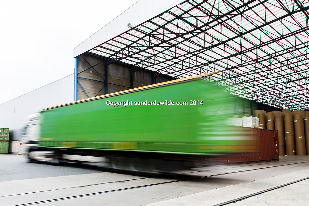 A green truck drives through in motion with paper at Van Moer Rail stock hall at the port of Antwerp on 8 may 2014