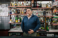 TARANTO, ITALY - 22 FEBRUARY 2018: Ignazio D'Andria, owner of the Mini Bar, chats with customers in Tamburi, the working-class district adjacent the ILVA steel mill in Taranto, Italy, on February 22nd 2018.<br /> <br /> Taranto, a  formerly lovely town on the Ionian Sea has for the last several decades been dominated by the ILVA steel mill, the largest steel plant in Europe. It was built by the government in the 1960s as a means of delivering jobs to the economically depressed south, but has been implicated for a cancer as dioxin and mercury have seeped into local groundwater, tainting the food supply, while poisoning the bay and its once-lucrative mussels.