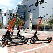 Motorized scooters sit on a busy corner in downtown Orlando on Monday, March 30, 2020 in Orlando, Florida. (Alex Menendez via AP)