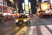 Yellow Taxi on City Street at Night