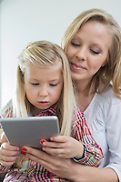 Loving woman with daughter using digital tablet at home