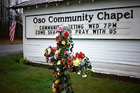 """A flower cross memorial is set up outside the Oso Community Chapel for mudslide victims in Oso, Washington March 27, 2014. Rescue teams on Thursday clawed through the moon-like surface left by a massive mudslide in Washington state that killed at least 25 people, searching for those still missing, and the community prayed for """"one little miracle.""""  REUTERS/Rick Wilking(UNITED STATES)"""