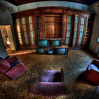 Lounge room in old house with three armchairs and old televisions