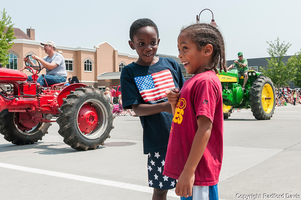 Boy and girl with braids at the Fourth of July parade in Ames, Iowa