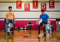 Ryan Vezina watches Justin Spencer of Recycled Percussion as they perform a drum duel for students and faculty during their surprise visit to Laconia Middle School Monday afternoon.  (Karen Bobotas/for the Laconia Daily Sun)