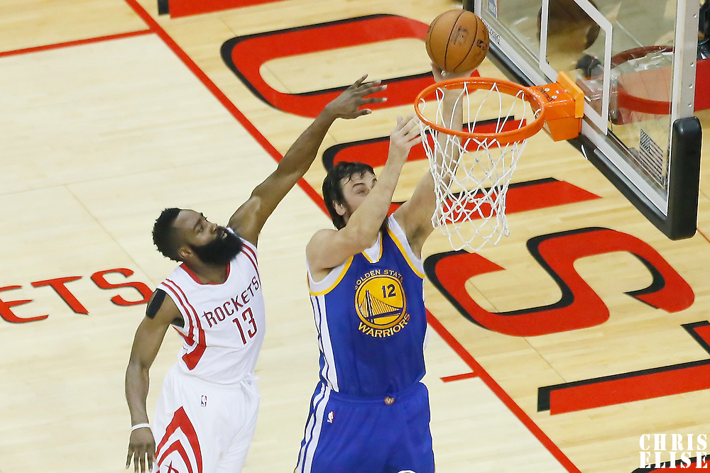 23 May 2015: Golden State Warriors center Andrew Bogut (12) goes for the layup past Houston Rockets guard James Harden (13) during the Golden State Warriors 115-80 victory over the Houston Rockets, in game 3 of the Western Conference finals, at the Toyota Center, Houston, Texas, USA.