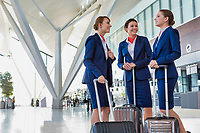 Portrait of young beautiful confident flight attendants talking in airport
