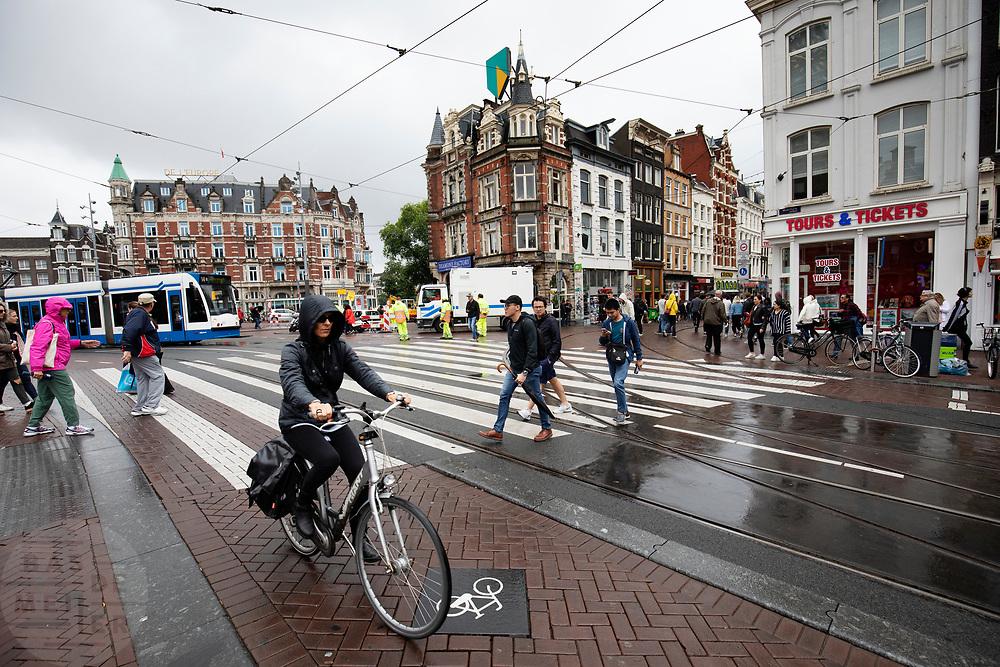 Een vrouw fietst door regen over het Muntplein in Amsterdam.<br /> <br /> A woman cycles in the rain at the Munt Square in Amsterdam.